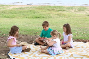 Children reading books outside having a picnic